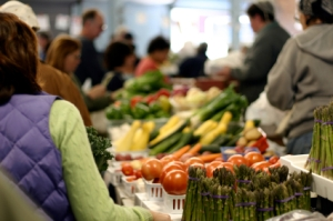 Fresh vegetables at farmers' market with shoppers and sellers milling about